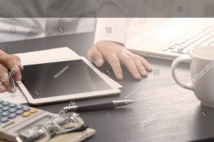 stock-photo-businessman-working-with-digital-tablet-computer-and-laptop-computer-on-wooden-desk-worm-tone-423622297_2